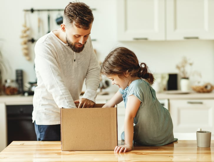 Kid and parent looking inside a box